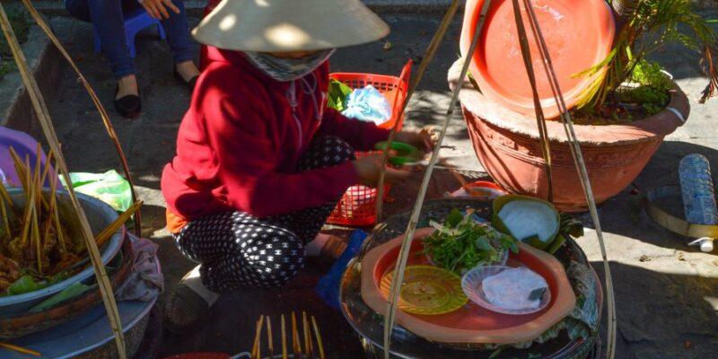 A street seller in Hoi An preparing food
